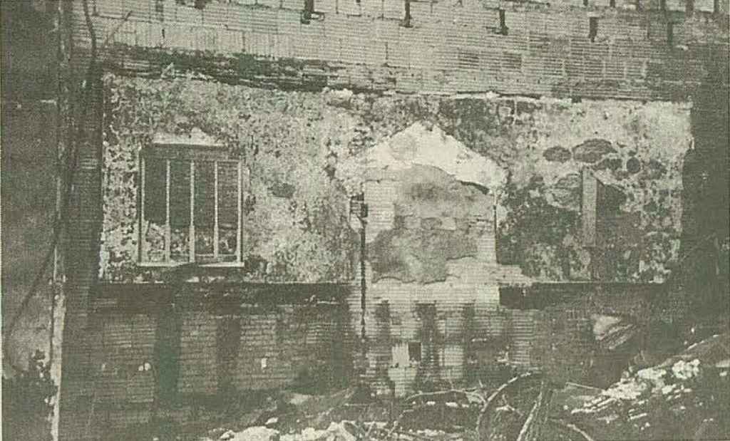 Photograph of the destroyed Homestead Hebrew Chapel in Beth Shalom (from 10/17/96 Chronicle). You can make out the melted yahrzeit plaques on either side.